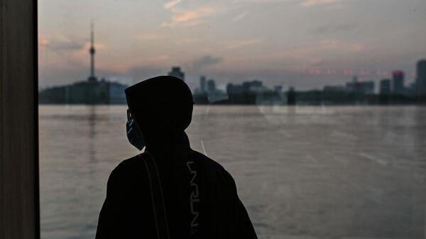 Человек в маске едет на пароме через реку Янцзы в Ухане, Китай