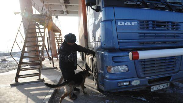 Осмотр автомобиля с собакой на многостороннем автомобильном пункте пропуска на российско-китайской границе между городами Забайльском и Маньчжурией