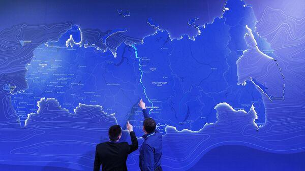 Мужчины у виртуальной карты Российской Федерации