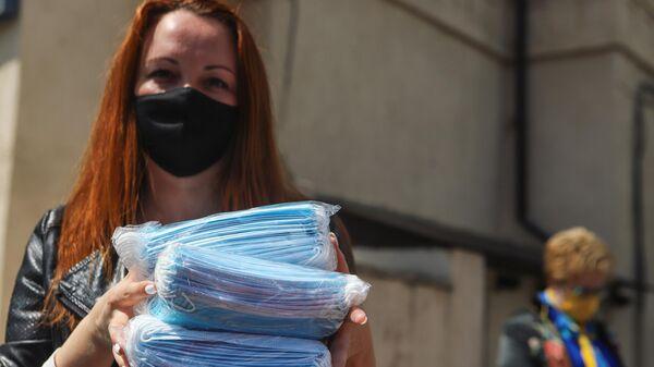 Волонтер держит в руках медицинские маски, выделенные Министерством труда и социальной защиты Ставропольского края