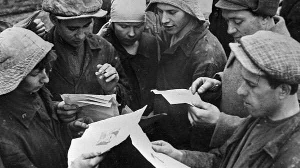 Группа комсомольцев-метростроевцев читает листовки, выпущенные выездной бригадой Комсомольской правды.