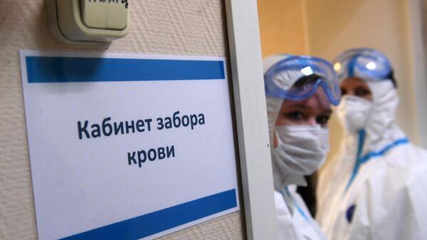 Медицинские работники в защитных костюмах у кабинета забора крови на наличие антител к COVID-19 в городской поликлинике Москвы