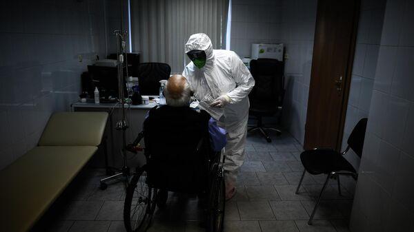 Врач осматривает пациента в центральной клинической больнице РЖД-Медицина в Москве, где проходят лечение больные с COVID-19