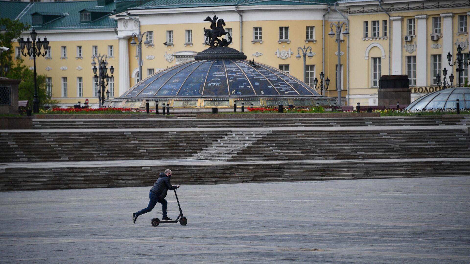 Мужчина едет на электросамокате по Манежной площади в Москве - РИА Новости, 1920, 10.06.2021