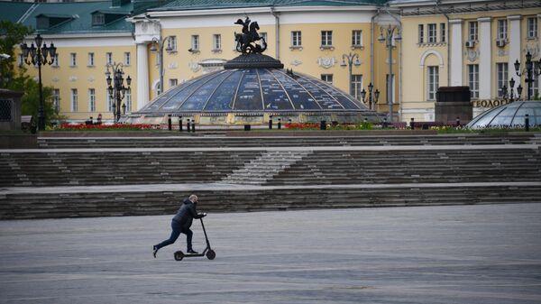 Мужчина едет на электросамокате по Манежной площади в Москве
