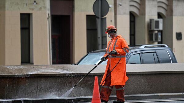 Сотрудник коммунальных служб моет бордюры на Кутузовском проспекте в Москве