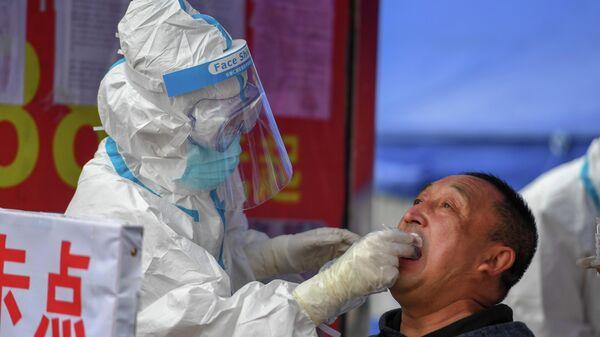 Медицинский работник делает тест на COVID-19 мужчине в провинции Цзилинь, Китай