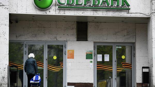 Женщина у входа в одно из отделений Сбербанка в Москве