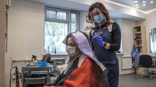 Девушке делают мелирование волос в салоне красоты
