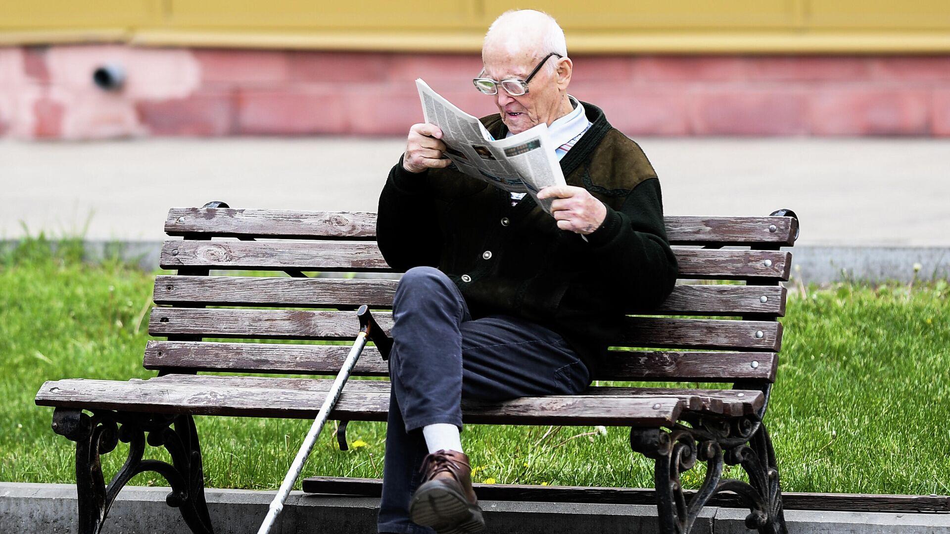 Мужчина читает газету на улице на лавочке в Москве - РИА Новости, 1920, 20.08.2020