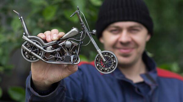 Мастер Станислав Черновасиленко демонстрирует миниатюрную копию модели мотоцикла Harley-Davidson Easy Rider Captain America