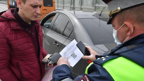 Инспектор ДПС проверяет цифровой пропуск у водителя
