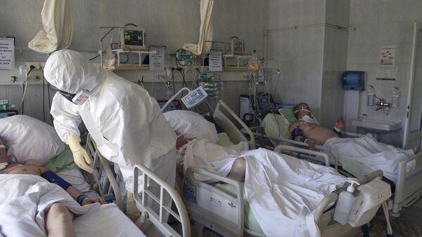 Медицинский работник возле постели пациента в отделении реанимации и интенсивной терапии