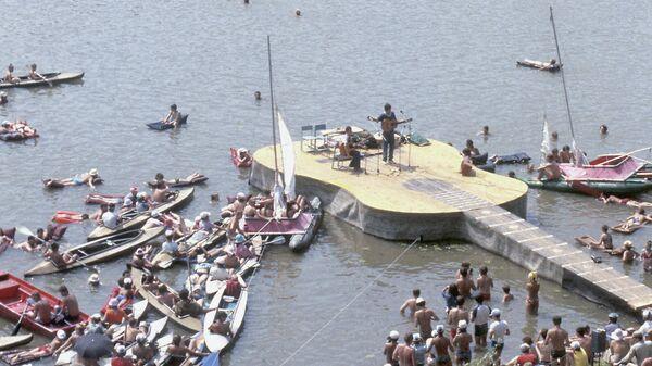 Участники 16-го фестиваля самодеятельной туристской песни в Самарской области выступают на эстраде, напоминающей по форме гитару.