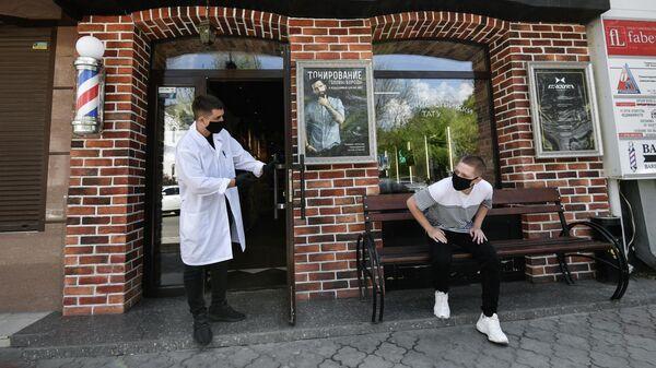Парикмахер приглашает клиента на стрижку в одной парикмахерских Симферополя