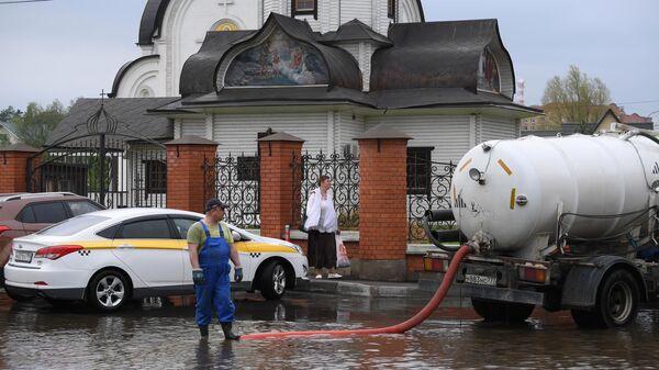 Ассенизаторская машина откачивает воду в поселке Нахабино Московской области