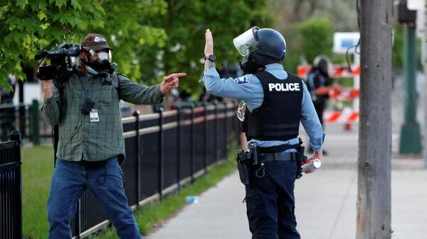 Журналист и сотрудник полиции во время акции протеста в Миннеаполисе, США