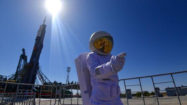 Мужчина в костюме космонавта фотографируется на фоне ракеты-носителя Союз-ФГ