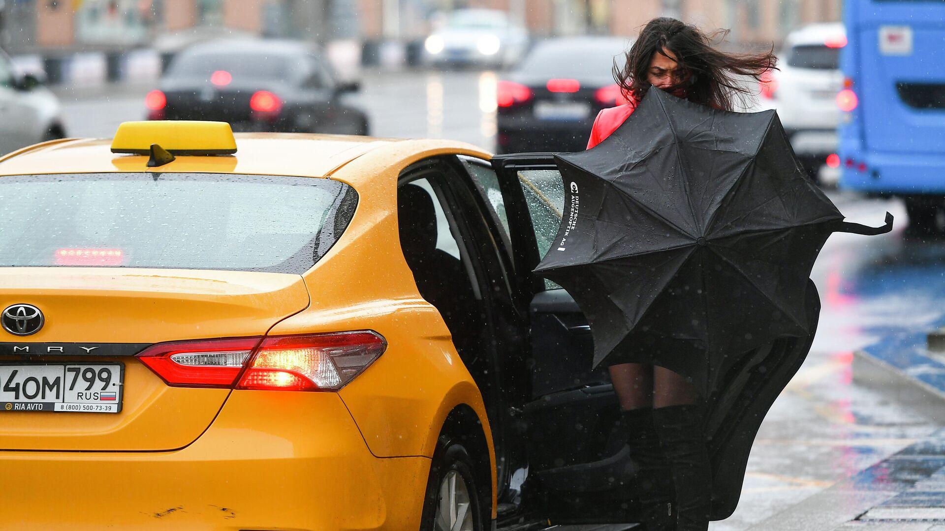 Девушка садится в такси во время дождя в Москве - РИА Новости, 1920, 07.02.2021