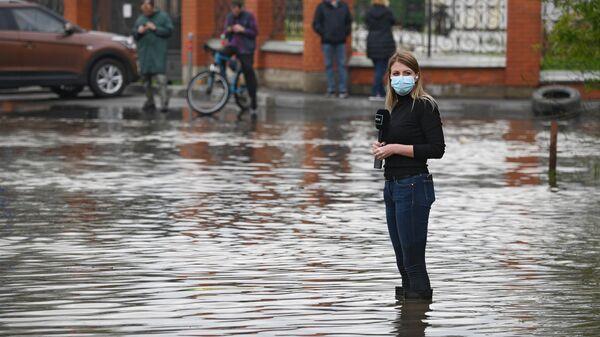 Корреспондент готовится к репортажу на затопленной улице в поселке Опалиха Московской области