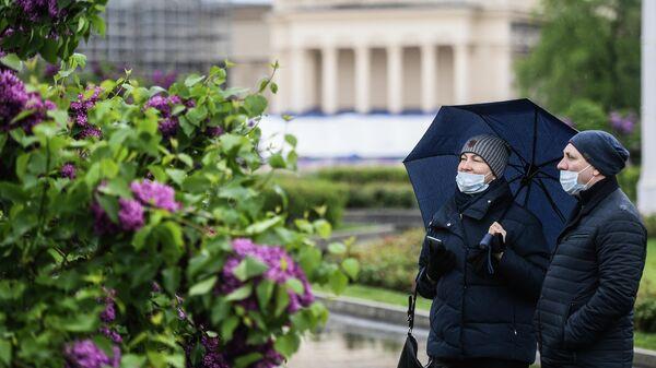 Прохожие гуляют на территории ВДНХ в Москве