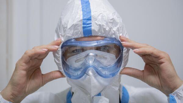 Медик надевает защитный костюм на входе в красную зону ГБУЗ ДГКБ им. З.А. Башляевой