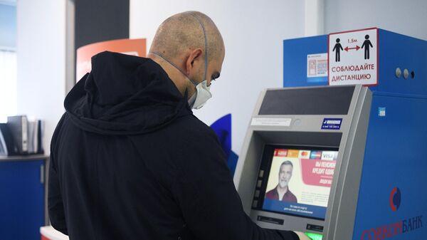 Клиент у терминала в отделении банка Совкомбанк в Москве