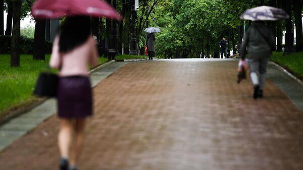 Прохожие гуляют по скверу у Чистых прудов в Москве