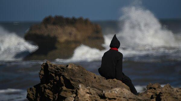 Мужчина смотрит на волны на берегу Атлантического океана в городе Эс-Сувейра