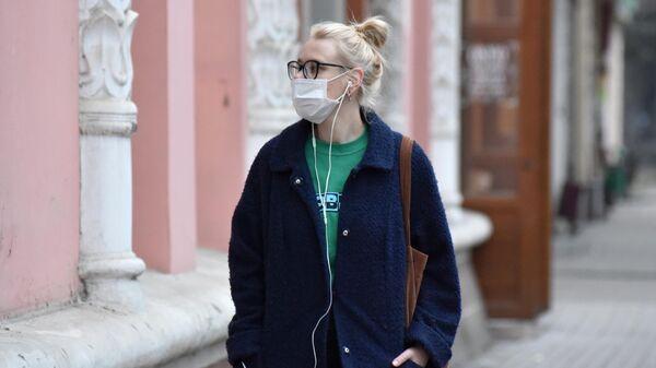 Девушка в защитной маске на одной из улиц в Пятигорске