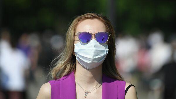 Девушка в медицинской маске в Центральном парке культуры и отдыха имени Горького в Москве