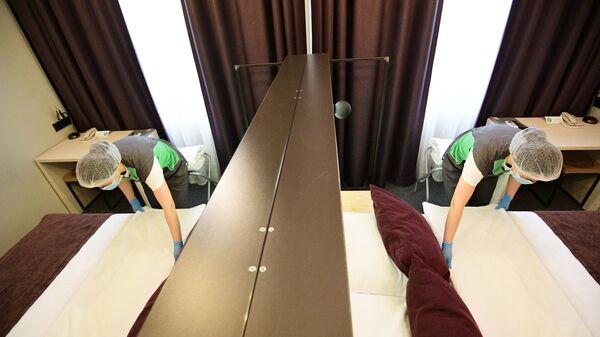 Горничная застилает кровать в номере отеля Library в Москве