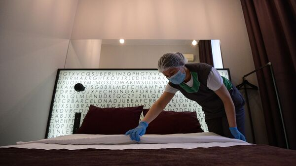 Горничная застилает кровать в номере отеля