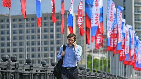 Прохожий на Новоарбатском мосту в Москве во время праздничных гуляний в честь празднования Дня России
