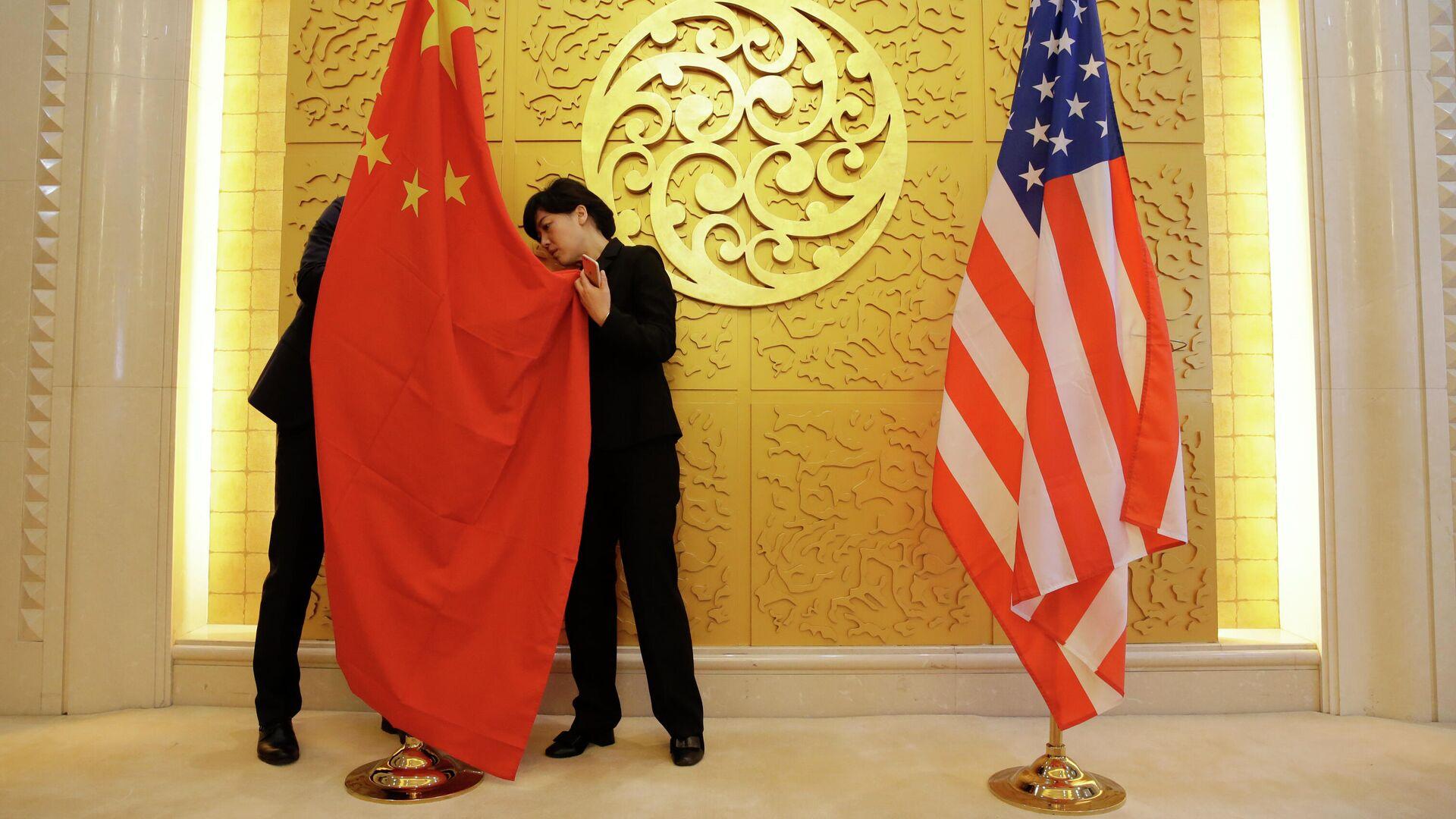 Служащие устанавливают флаг Китая перед встречей министров транспорта КНР и США - РИА Новости, 1920, 24.02.2021