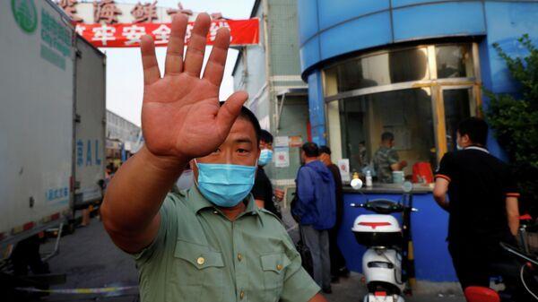 Охранник в маске возле рынка морепродуктов Jingshen в Пекине, Китай