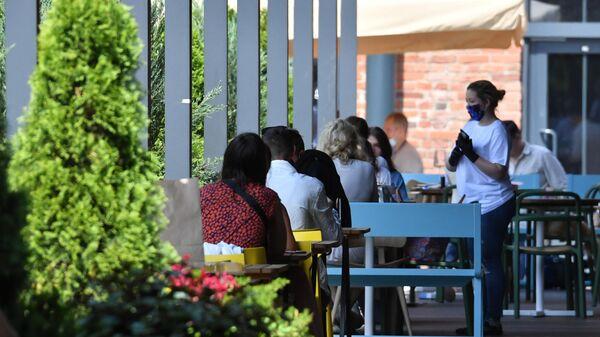 Посетители на летней веранде, расположенной на территории фудмолла Депо. Москва