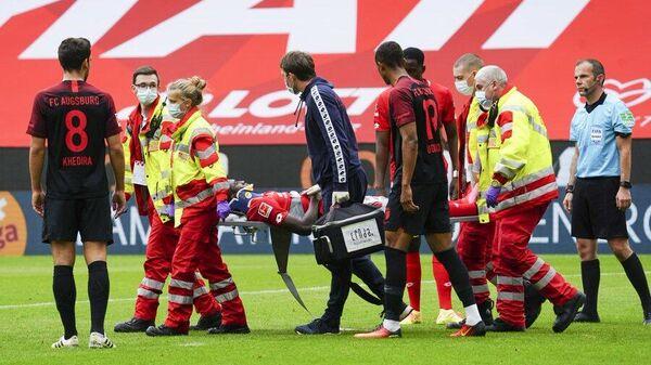 Медицинский персонал уносит нападающего Майнца Тайво Авонийи с поля после получения травмы