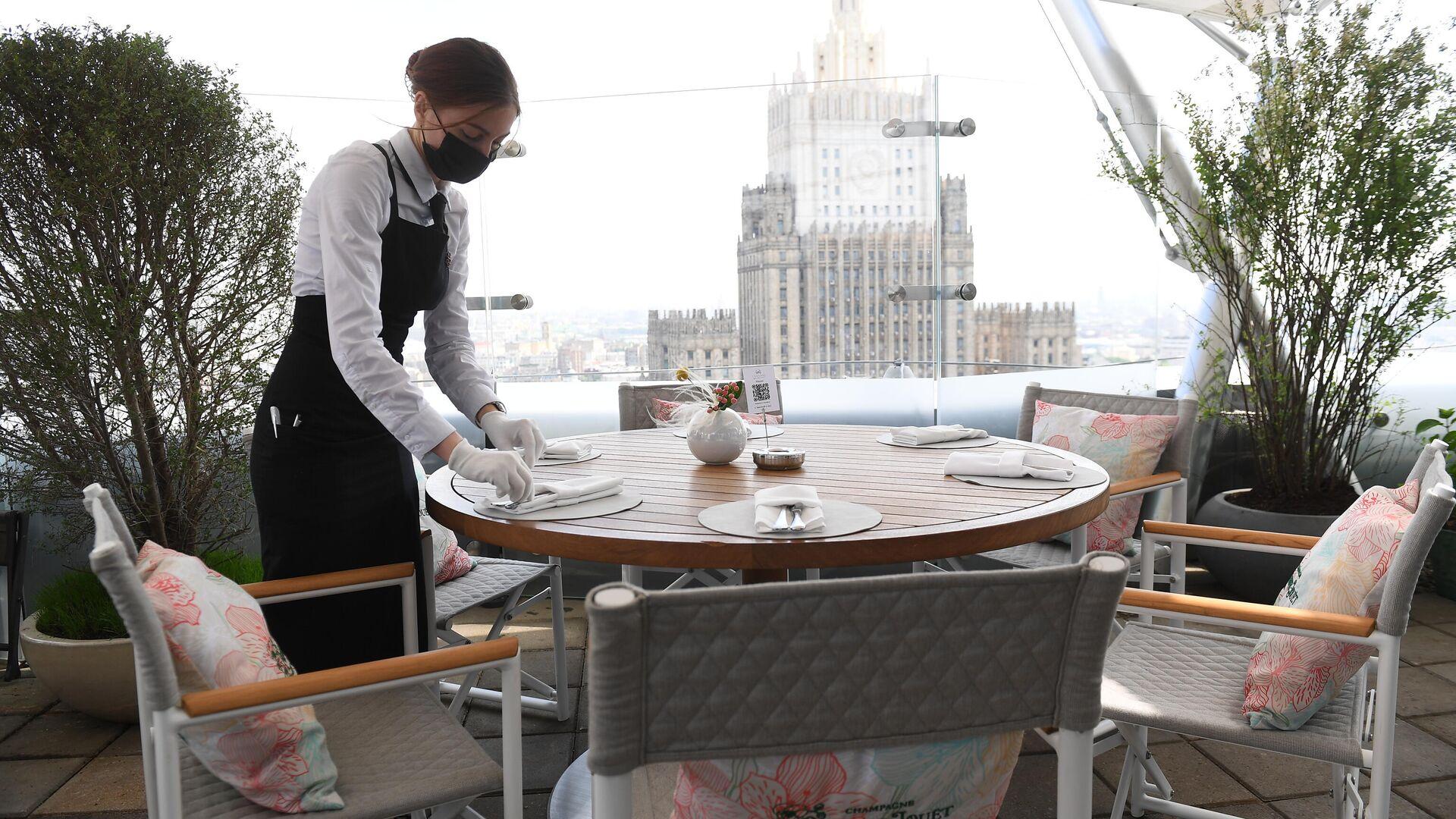 Официантка в защитной маске на открывшейся летней веранде ресторана Сахалин в Москве - РИА Новости, 1920, 27.09.2021