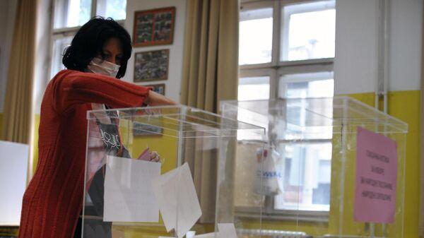 Женщина опускает бюллетень в урну для голосования на одном из избирательных участков Белграда