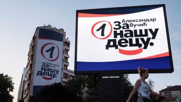 Женщина проходит мимо предвыборных плакатов правящей Сербской прогрессивной партии в Белграде
