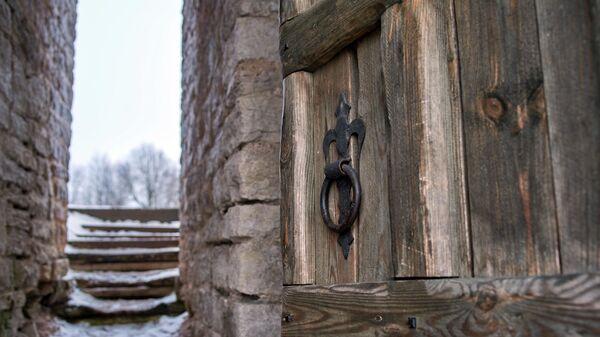 Деревянная дверь и лестница на территории Изборской крепости.