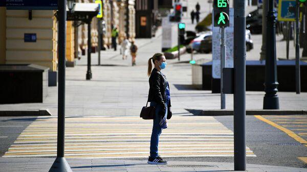 Девушка в медицинской маске и перчатках на одной из улиц в Москве