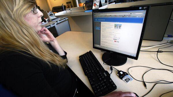Женщина сидит перед компьютером, чтобы проголосовать на всеобщих выборах в Эстонии. Таллин, 28 февраля 2011 года