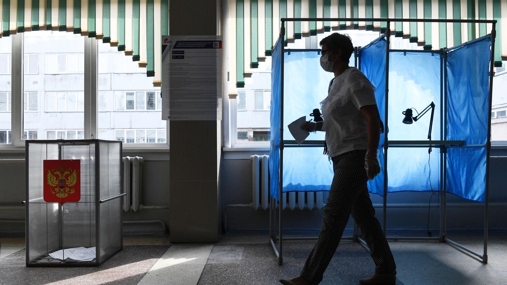 Женщина принимает участие в голосовании по внесению поправок в Конституцию РФ на избирательном участке №1503 в Новосибирске - РИА Новости, 1920, 08.02.2021