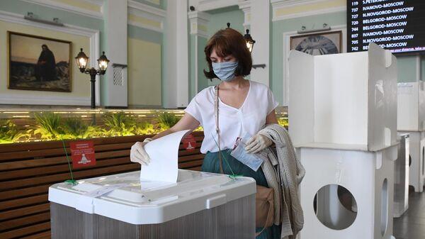 Женщина голосует по одобрению внесения поправок в Конституцию РФ на избирательном участке на Курском вокзале в Москве