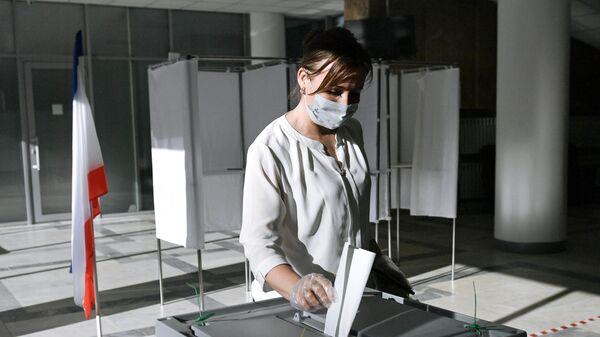 Женщина голосует по одобрению внесения поправок в Конституцию РФ на избирательном участке в Симферополе