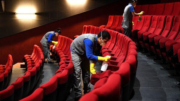Сотрудники клининговой службы производит санитарную обработку кресел в кинотеатре
