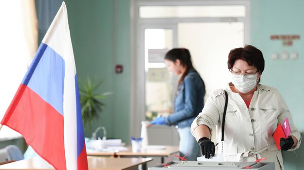 Женщина голосует по вопросу внесения поправок в Конституцию РФ