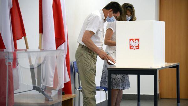 Избиратели во время голосования на выборах президента Польши на одном из избирательных участков в Варшаве